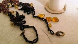 Beadwoven seed beads and crystals in black, old rose pink and yellows. :)