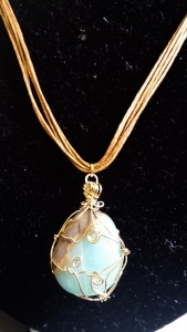 Materials:  Flat and triangular aqua stone with brown layer detail, gold wire, rustic brown multilayered cords
